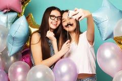 2 подруги с воздушными шарами colorfoul делают selfie на пэ-аш Стоковое Изображение