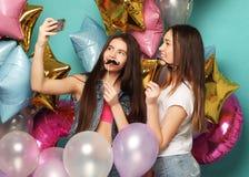 2 подруги с воздушными шарами colorfoul делают selfie на пэ-аш Стоковая Фотография