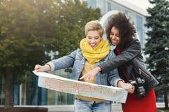 2 подруги outdoors с бумажной картой города Стоковое фото RF