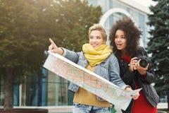 2 подруги outdoors с бумажной картой города Стоковые Фотографии RF