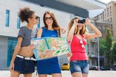 3 подруги outdoors с бумажной картой города Стоковые Изображения