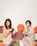 Подружки на софе с кружками кофе Стоковая Фотография