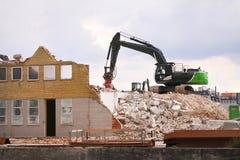 Подрывание здания с гусеницей на строительной площадке стоковые изображения