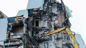 Подрывание старого здания, промежуток времени Экскаватор разрушает старое здание стоковое изображение