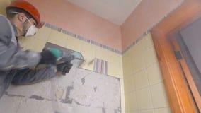 Подрывание старых плиток с jackhammer Реновация старых стен в bathroom или кухне сток-видео