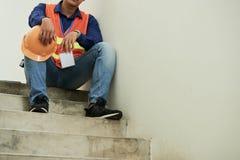 Подрядчик отдыхая на лестницах стоковые фото