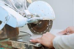 Подрядчик работая на плитке увидел отрезки мастера плитка на пиле Стоковое Фото