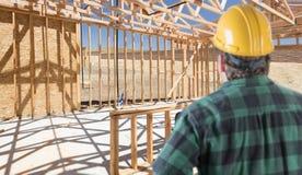 Подрядчик стоя внутренний обрамлять конструкции нового дома стоковое фото