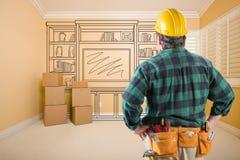 Подрядчик стоя внутри помещения при Moving коробки смотря линию Д-р стоковое фото
