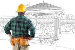 Подрядчик стоя смотрящ чертеж дизайна перголы патио стоковые изображения