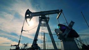 Подсвеченный масл-нагнетая деррик-кран в работая процессе Нефтедобывающая промышленность, нефтяная промышленность, концепция нефт сток-видео
