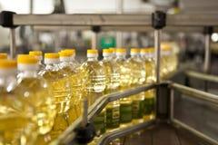 Подсолнечное масло в бутылке двигая дальше производственную линию Отмелый DOF стоковое фото