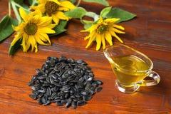 Подсолнечное масло в стеклянной шлюпке подливки, и пригорошня семян подсолнуха на предпосылке солнцецветов стоковая фотография