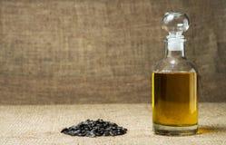 Подсолнечное масло в стеклянном графинчике, пуке семян подсолнуха на предпосылке мешковины стоковые фотографии rf