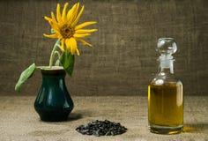 Подсолнечное масло в стеклянном графинчике, пук семян подсолнуха и солнцецвет в вазе на предпосылке мешковины стоковая фотография rf