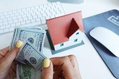 Подсчитывать деньги наличных денег для вклада недвижимости перед компьютером стоковое изображение