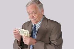 подсчитывающ его деньги вне Стоковое Изображение
