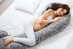 Подушка беременности Беременная женщина отдыхая на подушке тела стоковое изображение rf
