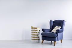 Подушка золота на голубом кресле Стоковое Фото