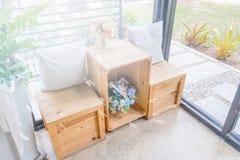 2 подушки на деревянном столе с деревянной табуреткой и вазами цветка Стоковая Фотография