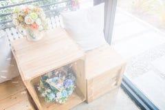 2 подушки на деревянном столе с деревянной табуреткой и вазами цветка Стоковые Фото