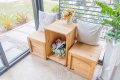 2 подушки на деревянном столе с деревянной табуреткой и вазами цветка Стоковое Изображение RF