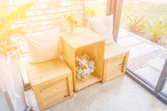2 подушки на деревянном столе с деревянной табуреткой и вазами цветка Стоковые Изображения RF