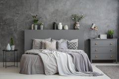 Подушки на кровати между таблицей и шкафом в острословии интерьера спальни Стоковое Изображение RF