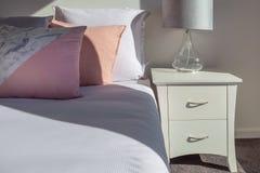 Подушки на кровати с белым прикроватным столиком Стоковые Фотографии RF