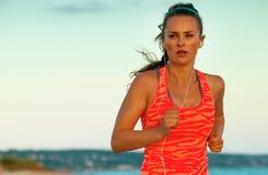 Подходящая активная женщина на пляже в jogging вечера Стоковое Изображение