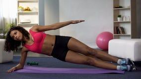 Подходящая девушка делая бортовую тренировку планки, разрабатывающ режим, строя вверх по мышцам стоковые изображения