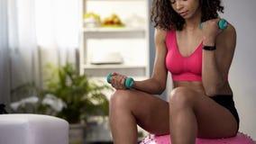Подходящая девушка сидя на шарике фитнеса и изгибая оружия, держа гантели, забота тела стоковые изображения