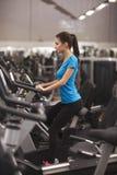 Подходящая женщина используя велосипед в фитнес-центре, cardio Портрет девушки фитнеса в спортзале Стоковая Фотография RF