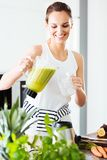 Подходящая женщина лить зеленый коктеиль стоковое фото rf
