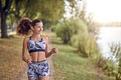 Подходящая здоровая атлетическая женщина jogging на речном береге Стоковая Фотография RF