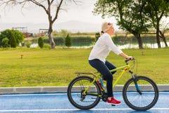 Подходящая здоровая женщина ехать велосипед в сельской местности Стоковые Изображения RF
