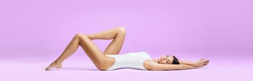 Подходящая и sporty девушка в нижнем белье Красивая и здоровая женщина представляя в белом купальнике Тонкое тело Спорт, фитнес,  стоковое фото rf