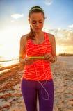 Подходящая спортсменка на береге моря с наушниками слушая к музыке Стоковые Фотографии RF