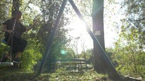 Подходящая счастливая женщина с длиной и тонизированные ноги нося спорт обувают отбрасывать в парке на летний день в замедленном  видеоматериал