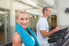 Подходящие молодые пары бежать на третбанах на спортзале стоковое изображение
