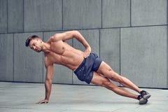Подходящий здоровый мышечный молодой человек при чуть-чуть комод делая бортовые планки стоковое фото rf