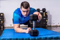 Подходящий молодой человек делая планку на спортзале Стоковые Фотографии RF