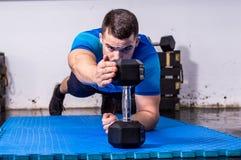 Подходящий молодой человек делая планку на спортзале Стоковые Фото