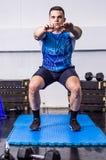 Подходящий молодой человек делая сидения на корточках на спортзале Стоковое Изображение RF