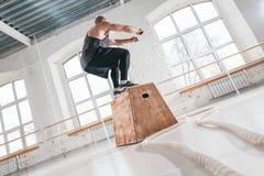 Подходящий мужской спортсмен делая тренировку скачки коробки в светлой зале стоковое фото rf