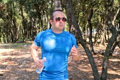 Подходящий мышечный человек бегуна jogging для фитнеса бежать на бежать следе в природе ландшафта outdoors Стоковые Фотографии RF