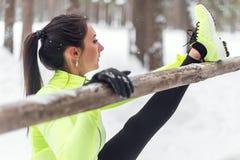 Подходящий спортсмен женщины делая ногу подколенного сухожилия протягивая тренировки outdoors в древесинах Работать женских спорт Стоковая Фотография RF