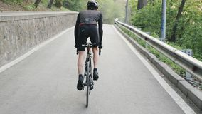 Подходящий сфокусированный велосипед велосипедиста pedaling из седловины гористой Сильные ноги с pedaling мышц Гористая тренировк видеоматериал