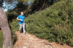 Подходящий человек бегуна jogging для фитнеса бежать на бежать следе в красивой природе ландшафта outdoors Стоковое Фото