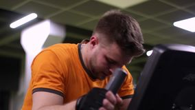 Подходящий человек разрабатывая на велотренажере на спортзале видеоматериал